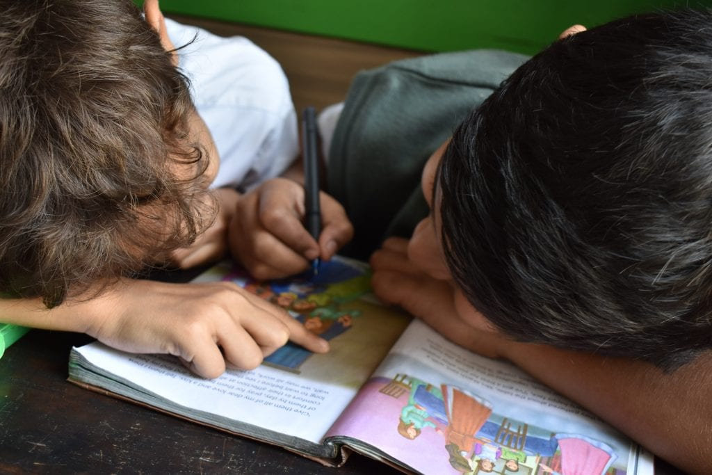 Two young kids reading, pointing to words in a book.