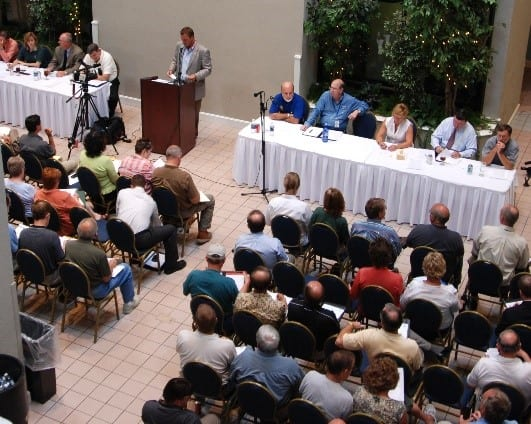 image of panel discussion with man talking at podium