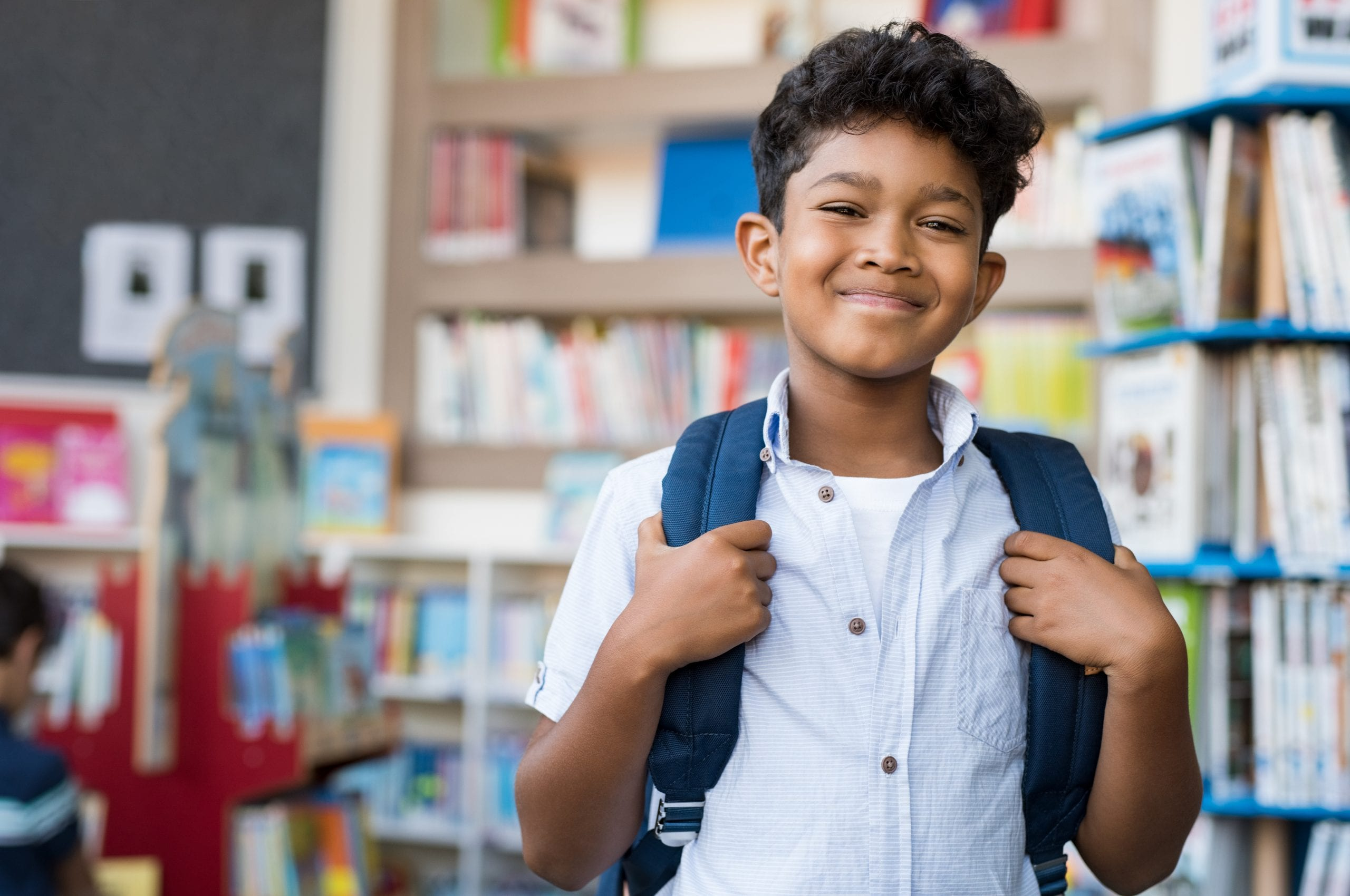 Young hispanic boy smiling with backpack on