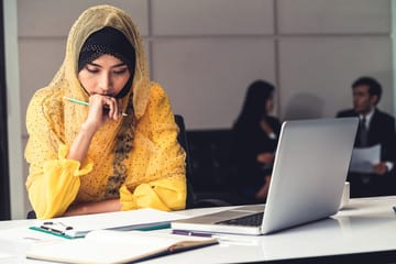 Young woman sitting at desk with computer a notepad