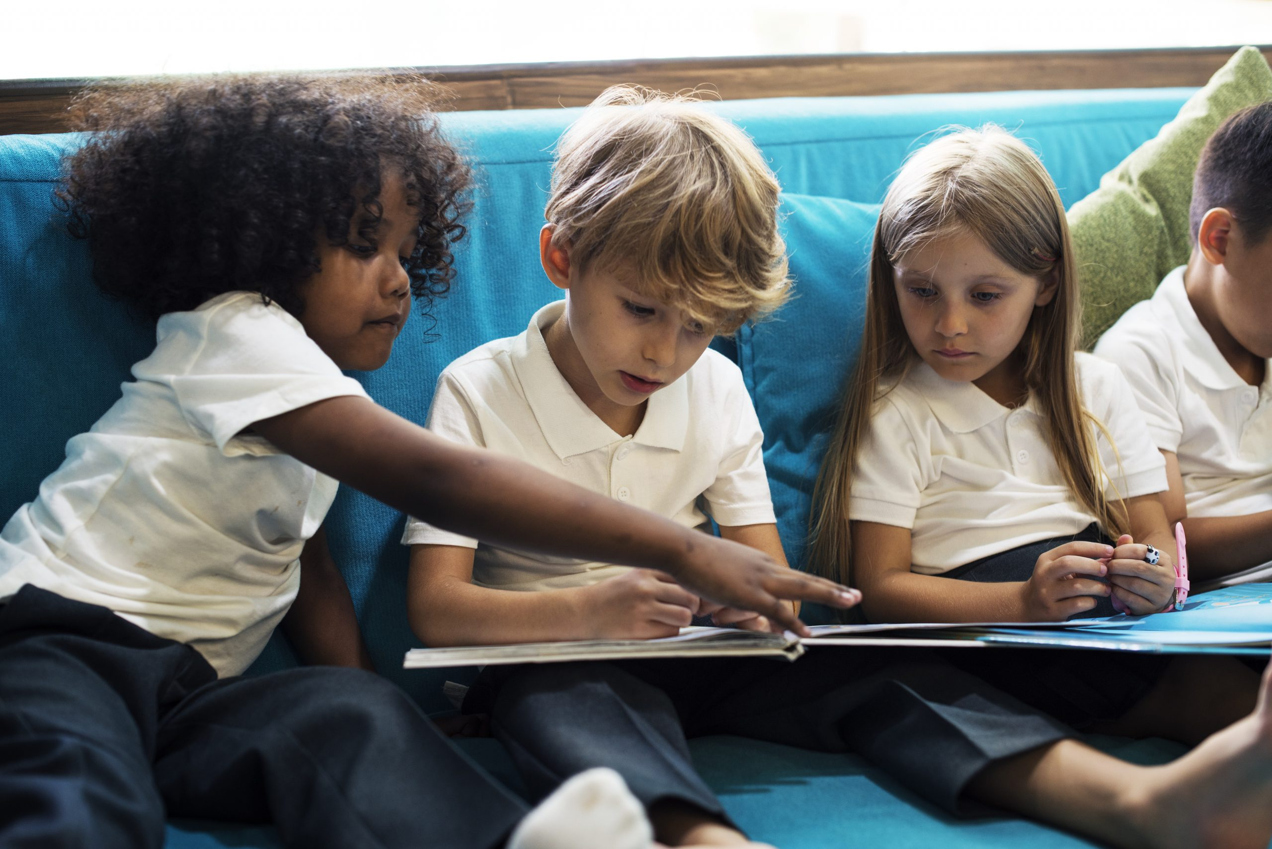 Group of Diverse Young Students Reading Children Story Book Together